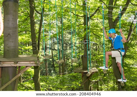 Sportsman is climbing inside high rope course - stock photo