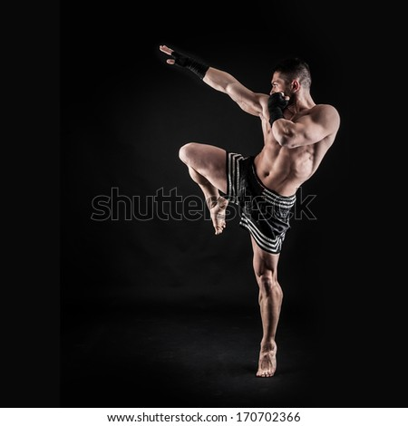 Sportsman kick boxer intense portrait against black background.  - stock photo