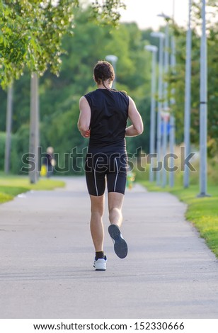 Sportsman running in park. Back view. - stock photo