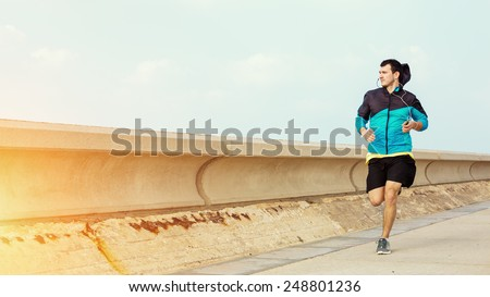 sportsman running near concrete fencing and looking far away - stock photo