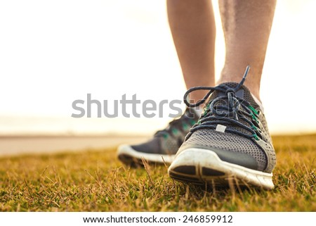 sportsman's legs standing on the grass in running shoes close up - stock photo