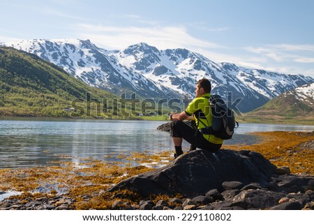 Sportsman  sitting on lakeside with snow mountains on background, Norway - stock photo