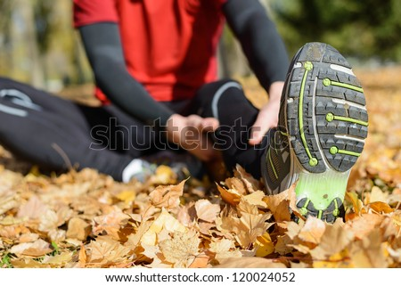 Sportsman stretching painful femoral leg muscle. Sport and injury prevention concept on autumn park outside.