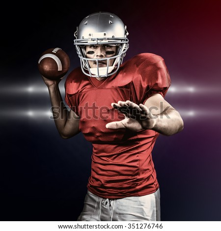 Sportsman throwing American football while playing against spotlights - stock photo