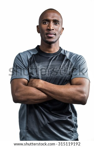 Sportsman with arms crossed standing against white background