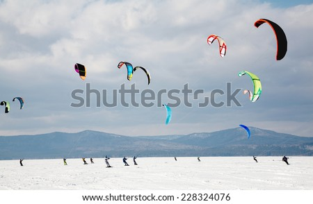 Sportsmen snowkiting at sport winter competition - stock photo