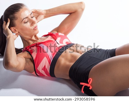 sportswoman doing exercise, abs crunch isolated on white background - stock photo