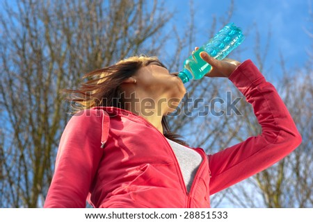 Sportswoman drinking water in a park. View from below. - stock photo