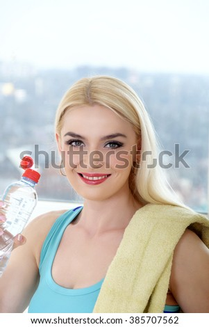 Sportswoman drinks water from a plastic bottle. Concept: sports, fitness at home, shaping, aerobics, healthy lifestyle. - stock photo