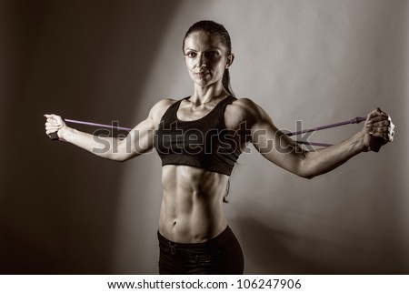 Sportswoman exercising with a resistance band. Black and white photo - stock photo