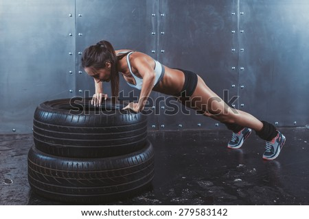 Sportswoman. Fit sporty woman doing push ups on tire strength power training concept crossfit fitness workout sport and lifestyle  - stock photo
