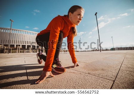 Sportswoman in ready position to run.Girl on the knee, preparing to start jogging.Achievements and goals