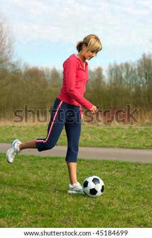 Sportswoman kicking  a ball  (playing football outdoors). - stock photo