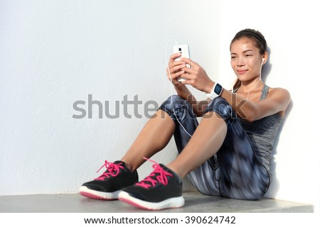 Sportswoman listening to music using phone app and smartwatch fitness activity tracker - heart rate monitor tracking her health progress on smartphone. Asian athlete in sportswear fashion clothing. - stock photo