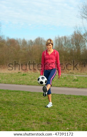 Sportswoman playing outdoors with a ball.