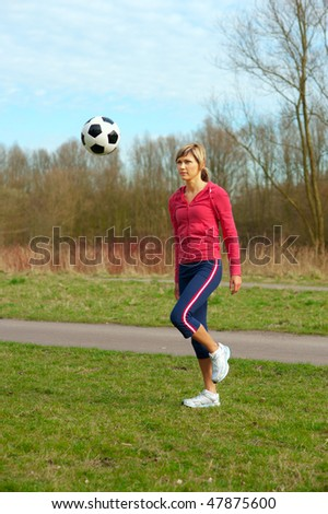 Sportswoman playing outdoors with a ball. - stock photo