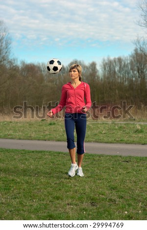 Sportswoman playing outdoors with a ball, throwing it up. - stock photo