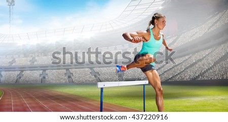Sportswoman practising the hurdles against view of a stadium