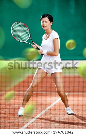 Sportswoman returning lots of balls at the tennis court. Concept of tournament preparation and healthy lifestyle - stock photo