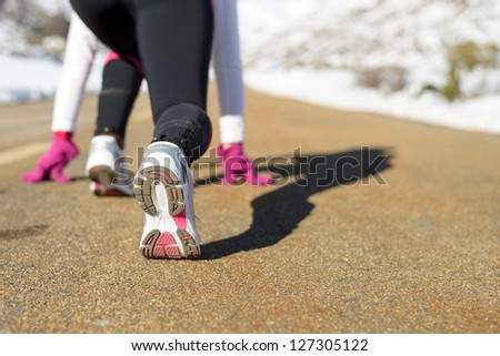Sportswoman running on winter concept. Female athlete ready to run on mountain snowy road. Copy space. - stock photo
