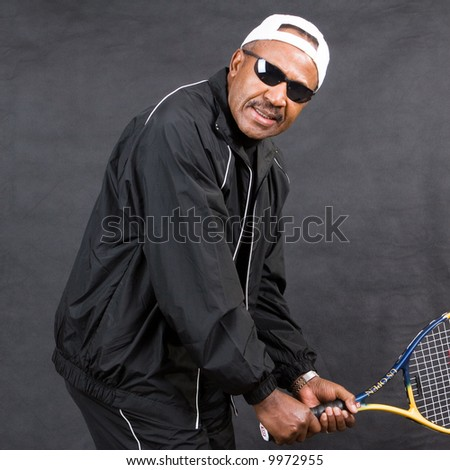 sporty african american senior playing tennis