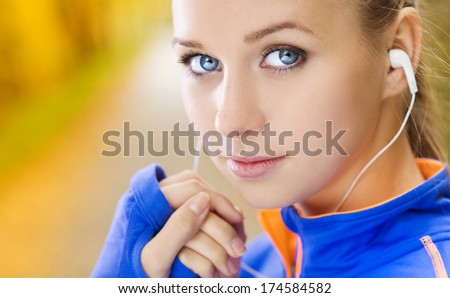 Sporty and active woman runner is listening to music before outdoor exercise - stock photo