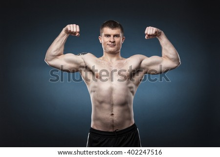 Sporty and healthy muscular man isolated on dark blue background - stock photo