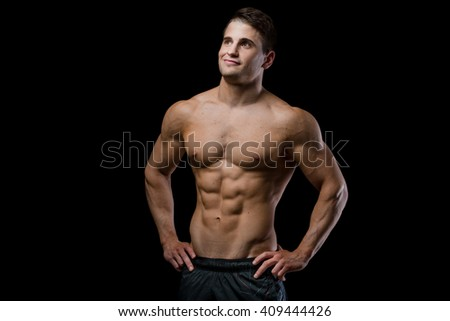 Sporty and healthy muscular man looking up isolated on black background