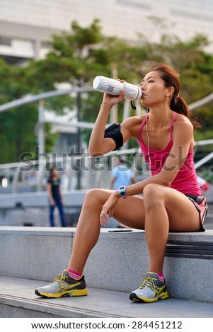 sporty asian chinese woman sitting outdoors resting drinking water bottle after morning run - stock photo