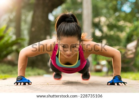 Sporty Asian woman doing push-ups outdoors  - stock photo