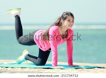 sporty asian woman warming up stretch her legs in the beach