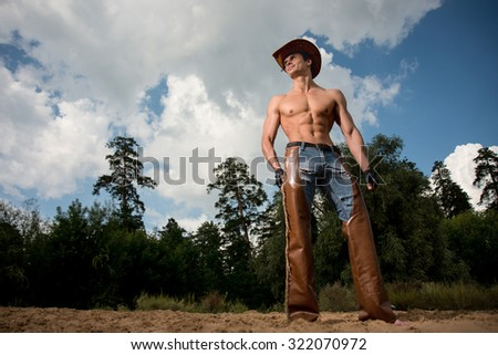 sporty, athletic, muscular sexy man in a cowboy outfit - stock photo