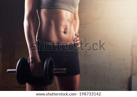 Sporty athletic woman ready for hard training with dumbbells - stock photo