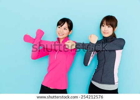 sporty attractive woman stretching on blue background - stock photo