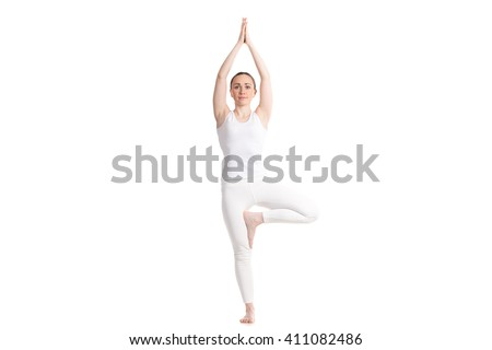 Sporty attractive young woman in white sportswear doing exercise for spine, Vrikshasana pose, hands above the head in Anjali mudra, part of large photo series, isolated, full length, front view - stock photo