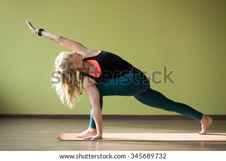 Sporty beautiful blond woman in sportswear working out indoors, doing lunge exercise for hips and spine flexibility, standing on orange eco mat in Parivrtta Parsvakonasana yoga pose, full length - stock photo