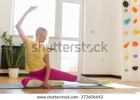 Sporty beautiful blond woman in sportswear working out indoors, doing lunge exercise for hips and spine flexibility. - stock photo
