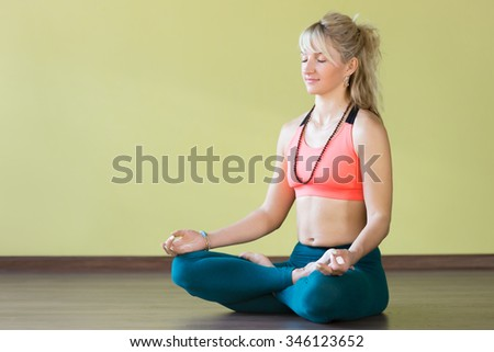 Sporty beautiful blond woman in sportswear working out indoors, sitting cross-legged in Padmasana, Lotus posture, asana for meditation, breathing exercises, fingers in Jnana mudra, full length - stock photo