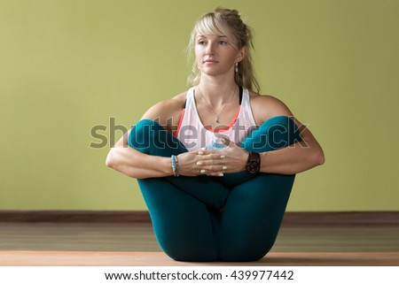 Sporty beautiful blond young woman in sportswear working out indoors, doing variation of Garbha Pindasana - Womb Embryo Pose on orange eco mat, full length - stock photo