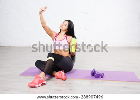 Sporty beautiful long hair brunette young woman making selfie photo on smartphone during workout break.  - stock photo