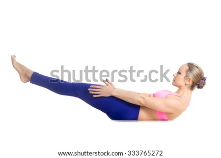 Sporty beautiful young blond woman doing exercises for abs, Ardha navasana, half boat pose, studio full length isolated shot, profile view on white background