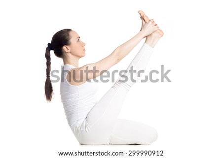 Sporty beautiful young woman in white sportswear doing exercises for legs, sitting in Heron Pose, studio full length isolated shot, side view, part of large photo series