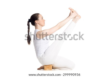Sporty beautiful young woman in white sportswear doing exercises for legs using block, sitting in Krounchasana Pose, studio full length isolated shot, side view