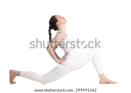 Sporty beautiful young woman in white sportswear doing low lunge exercise, variation of anjaneyasana, ashva sanchalasana, profile view, studio full length shot, isolated