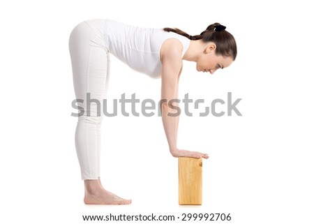 Sporty beautiful young woman in white sportswear doing variation of Standing Half Forward Bend, Ardha Uttanasana pose with wooden blocks, studio full length shot on white background, isolated - stock photo