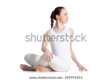 Sporty beautiful young woman in white sportswear practicing yoga, sitting cross legged in Revolved easy pose, spinal twist, parivrtta sukhasana, studio full length isolated shot, three-quarters view - stock photo