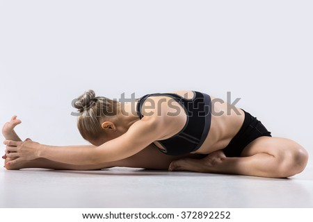 Sporty beautiful young woman practicing yoga, doing Janu Sirsasana, Head-to-Knee Forward Bend Pose, working out wearing black sportswear, studio, full length - stock photo