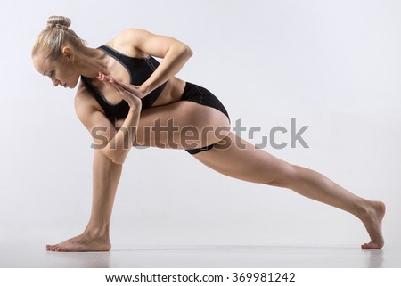 Sporty beautiful young woman practicing yoga, doing lunge exercise, Revolved Side Angle Pose, Parivrtta Parsvakonasana, working out wearing black sportswear, studio full length, grey background