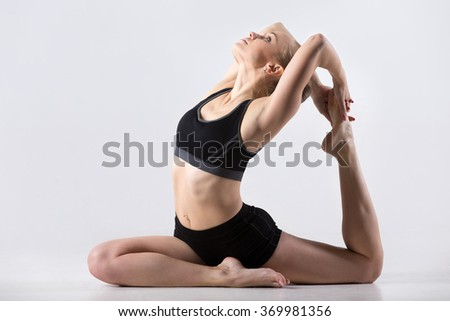 Sporty beautiful young woman practicing yoga, doing One Legged King or Royal Pigeon Pose - Eka Pada Rajakapotasana, working out wearing black sportswear, studio, full length - stock photo