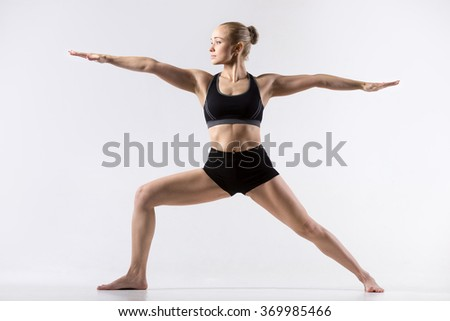 Sporty beautiful young woman practicing yoga, standing in Warrior II posture, Virabhadrasana Two pose, working out wearing black sportswear, studio full length, grey background - stock photo